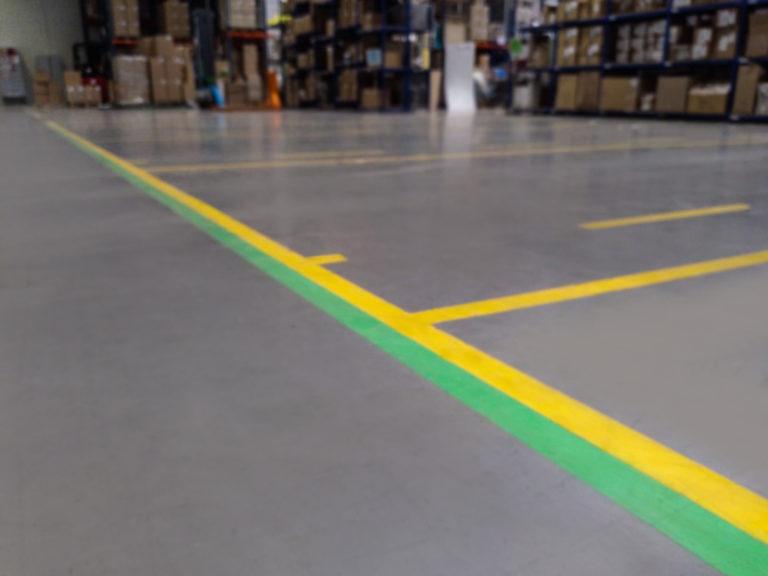 Znakowanie ciągów komunikacyjnych to kluczowy element BHP na hali produkcyjnej.
